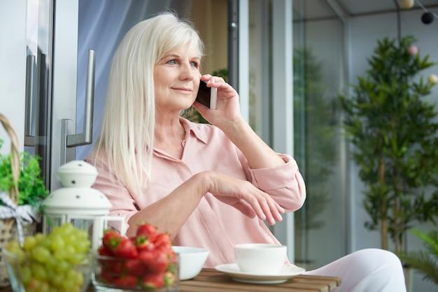 Gros plan sur femme mûre bénéficiant d'un bon café sur le balcon