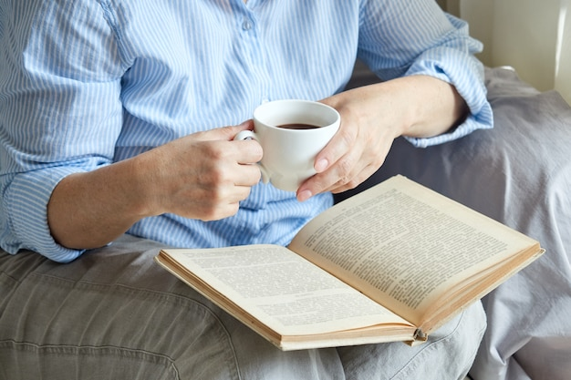 Gros plan d'une femme mûre lisant un livre à la maison près de la fenêtre, assise sur le canapé avec une tasse de café.