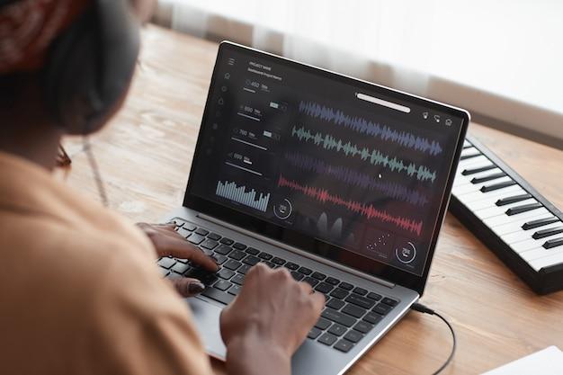Gros plan d'une femme musicienne afro-américaine à l'aide d'un ordinateur portable avec un logiciel d'édition sonore tout en composant de la musique à la maison, copiez l'espace