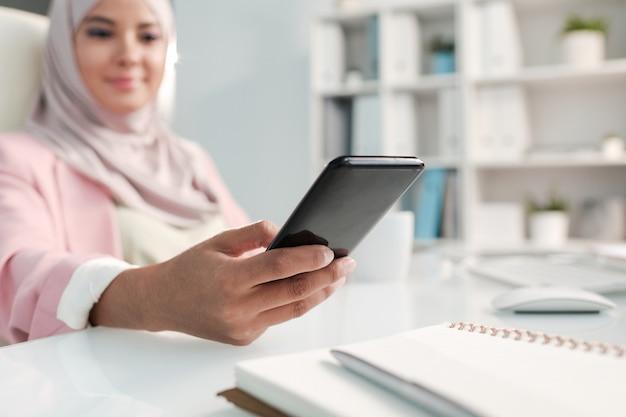 Gros plan d'une femme musulmane à l'aide de smslartphone tout en répondant à des sms au bureau
