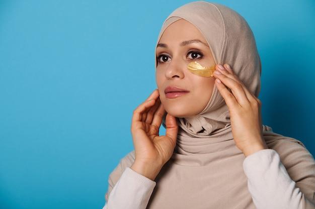 Gros plan d'une femme musulmane en hijab à l'aide de patchs oculaires hydrogel. portrait de beauté