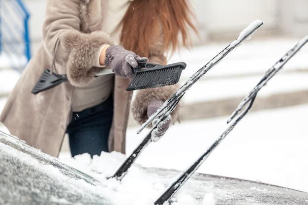 Gros plan d'une femme nettoyant les essuie-glaces de la neige avec une brosse