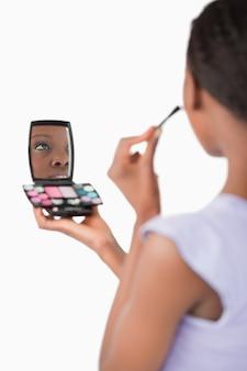 Gros plan de la femme de l'ombre tout en appliquant le maquillage contre un whi