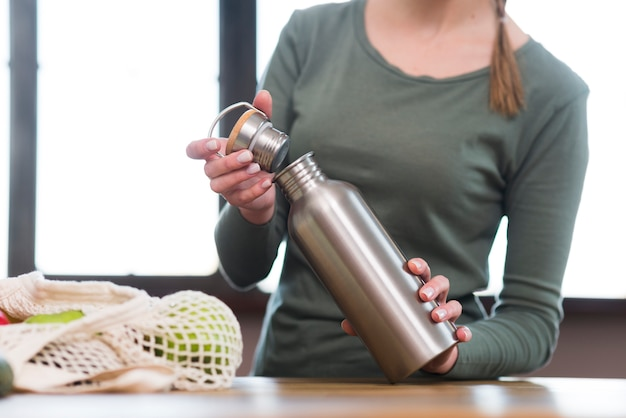 Gros plan, femme, ouverture, bouteille, thermos