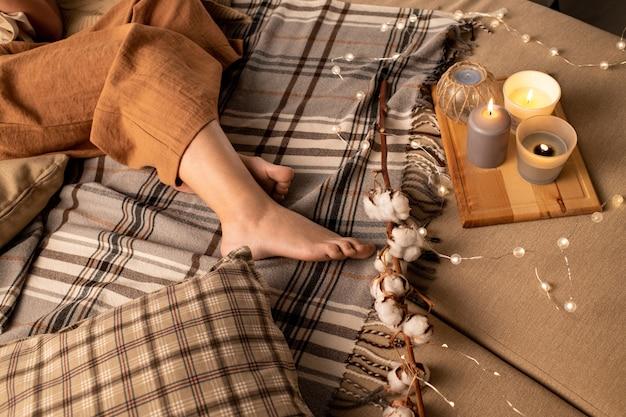 Gros plan de femme en pantalon beige allongé sur le lit avec des bougies aromatiques sur plateau