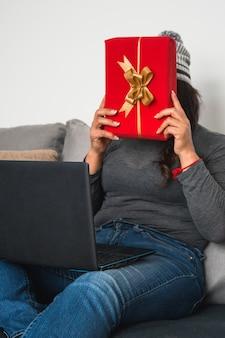 Gros plan d'une femme parlant à ses amis sur un ordinateur portable et leur montrant une boîte-cadeau rouge