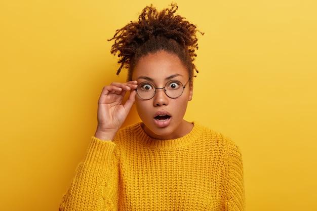 Gros plan d'une femme à la peau sombre stupéfaite réagit à des nouvelles surprenantes, garde la main sur le bord des lunettes