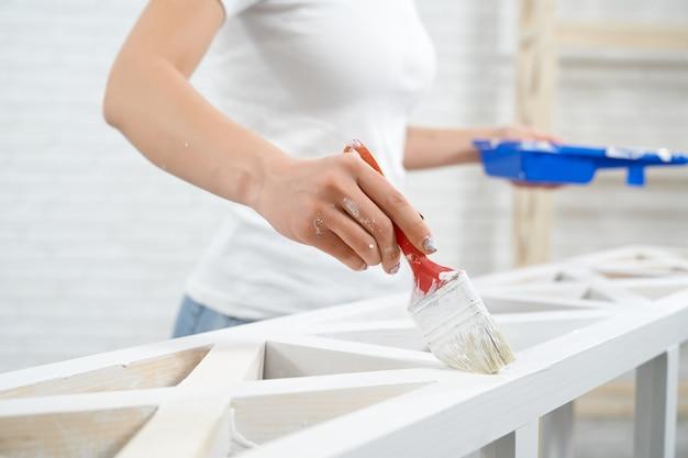 Gros plan d'une femme peignant avec un support de rangement de couleur blanche