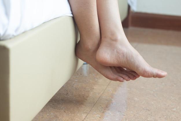 Gros plan femme pied pied est assis sur le lit se détendre concept
