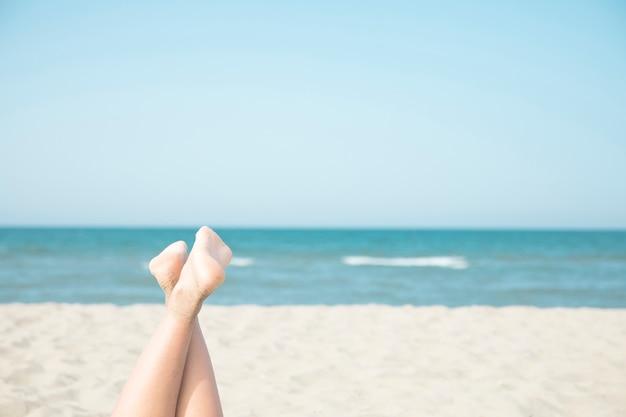 Gros plan femme pieds au bord de la mer