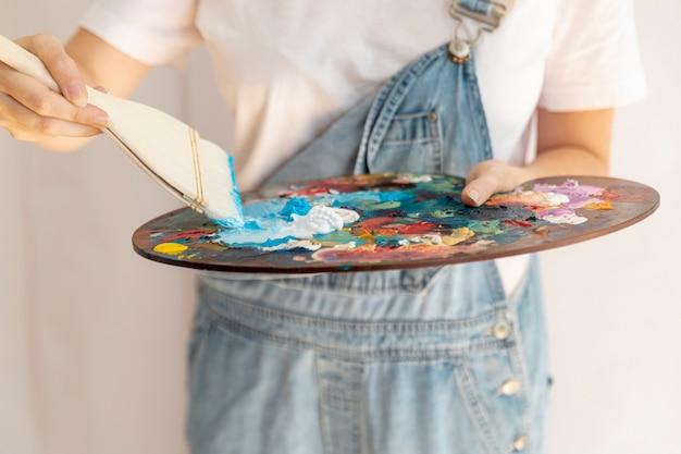 Gros plan femme avec pinceau et palette