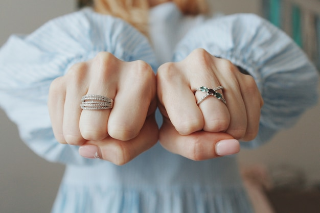 Gros plan d'une femme portant de beaux anneaux sur les deux mains et montrant avec les poings