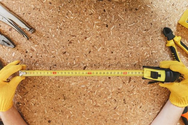 Gros plan sur une femme portant des gants jaunes travaillant dans un atelier de menuiserie sur une table en bois avec différents outils, mesurant la longueur par un ruban à mesurer. vue de dessus. copiez l'espace pour la publicité. avec place pour le texte.