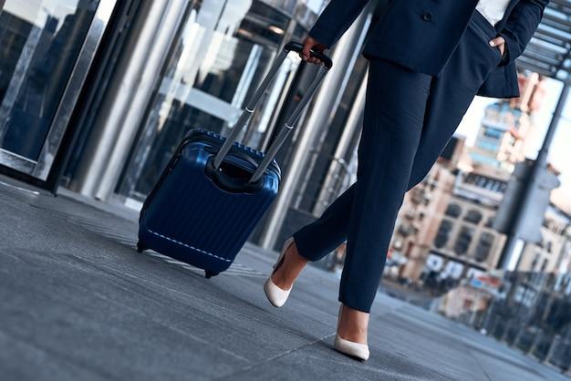 Gros plan d'une femme portant une valise au terminal de l'aéroport