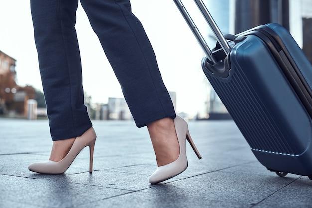 Gros plan d'une femme portant une valise au terminal de l'aéroport et