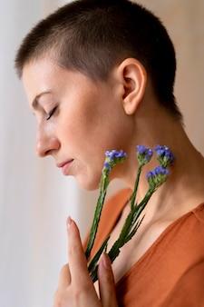 Gros plan femme posant avec des fleurs