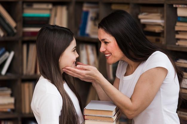 Gros plan femme positive et jeune fille à la bibliothèque