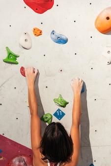 Gros plan d'une femme pratiquant l'escalade sur un mur artificiel à l'intérieur. mode de vie actif et concept de bloc.