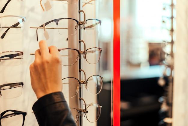 Gros plan d'une femme prenant des lunettes d'étagère.