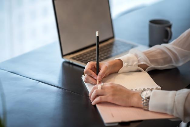 Gros plan de femme prenant des notes sur le bureau au bureau