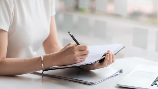 Gros plan d'une femme prenant des notes avec un ordinateur portable à la maison.