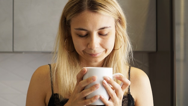 Gros plan d'une femme prenant une odeur de café avec les yeux fermés