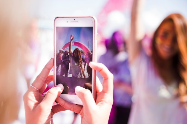 Gros plan femme prenant la photo de son amie sur téléphone mobile
