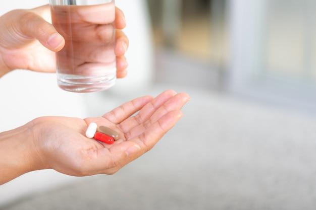 Gros plan de femme prenant en pilule, concept de médecine, de soins de santé et de personnes.