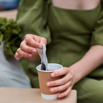 Gros plan, femme, prendre, sachet thé, hors tasse