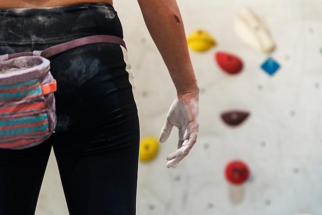 Gros plan d'une femme prête à pratiquer l'escalade sur mur artificiel à l'intérieur. mode de vie actif et concept de bloc.