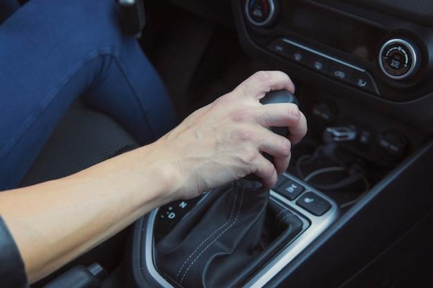 Gros plan sur une femme qui change de vitesse sur une boîte de vitesses automatique et une voiture au volant. la main féminine déplace l'hydro assis dans un véhicule. entreprise automobile, vente de voitures, consumérisme, transport et concept de voyage.