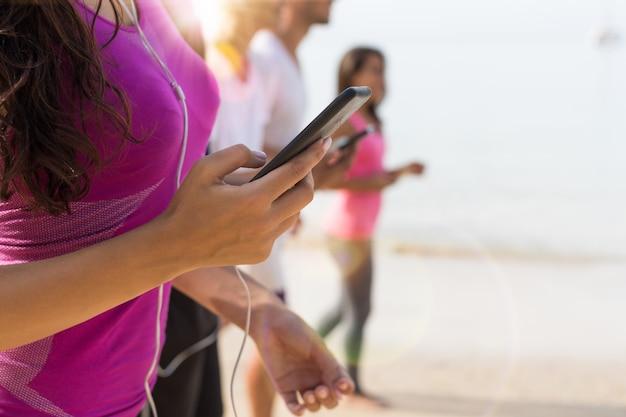 Gros plan d'une femme qui court sur la plage à l'aide d'un téléphone intelligent