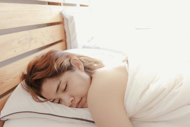 Gros plan d'une femme qui dort sur son lit blanc concept de somnolent