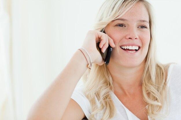 Gros plan d'une femme qui rit sur son téléphone alors qu'elle regarde sur le côté