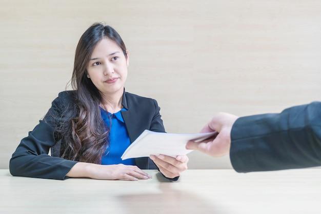 Gros plan d'une femme qui travaille reçoit un document de travail de son patron avec un visage qui ne veut pas