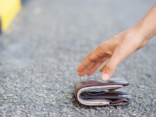 Gros plan, femme, ramasser, déchiré, portefeuille, bord route