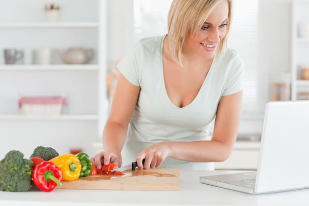 Gros plan d'une femme à la recherche d'une recette sur un ordinateur portable