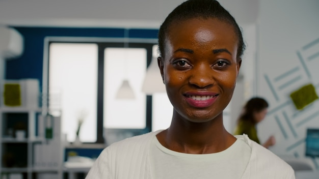 Gros plan d'une femme regardant la caméra souriante debout dans le bureau de l'agence de création de démarrage tenant un ordinateur portable, en tapant dessus