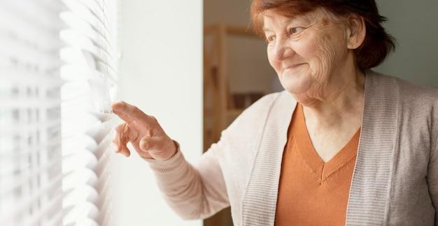 Gros plan femme regardant par la fenêtre