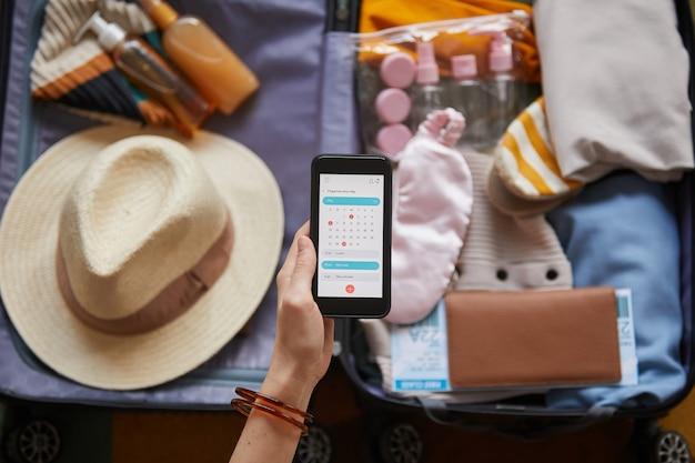 Gros plan, de, femme regarde, calendrier, dans, elle, téléphone portable, tout, emballer, vêtements, dans, vacances