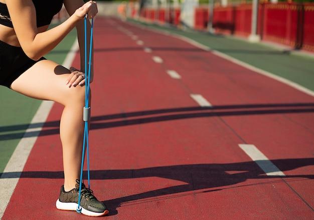 Gros plan d'une femme de remise en forme faisant de l'exercice pour les jambes avec une bande de résistance en caoutchouc. espace pour le texte