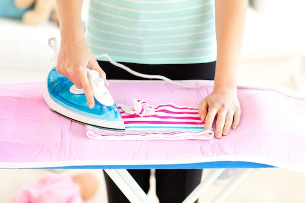 Gros plan d'une femme repassant ses vêtements
