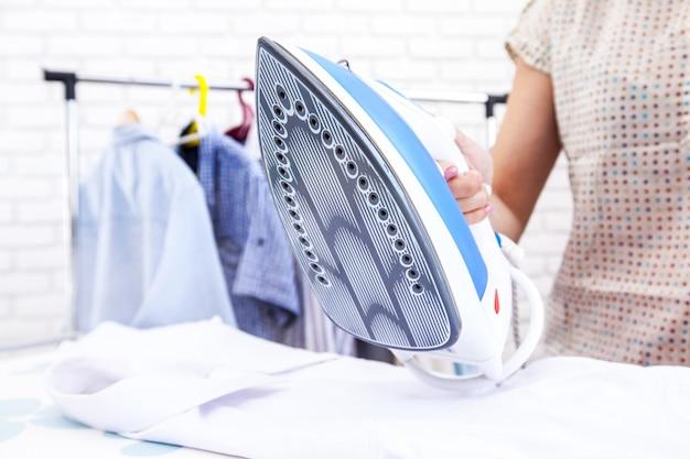 Gros plan d'une femme repassant des vêtements sur la table