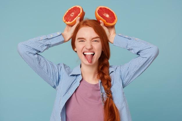 Gros plan d'une femme rousse drôle ludique montre la langue faisant des cornes avec deux tranches de pamplemousse