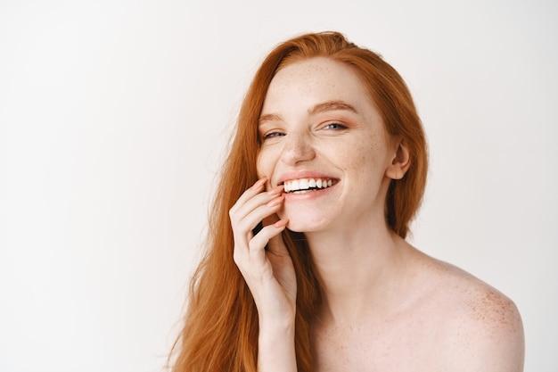 Gros plan d'une femme rousse heureuse à la peau pâle et parfaite, riant et montrant des dents blanches, debout nue sur le mur du studio