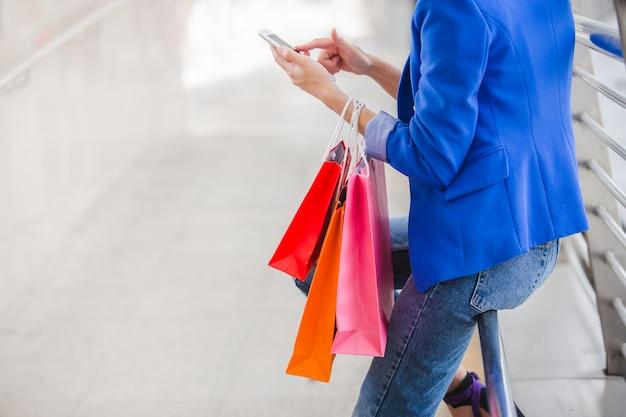 Gros plan de femme avec des sacs à provisions à l'aide d'un smartphone