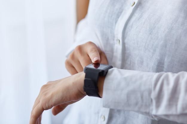 Gros plan d'une femme sans visage en fille de vêtements blancs utilisant sa montre intelligente, touchant l'écran tactile tout en posant près de la fenêtre.