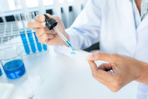 Gros plan d'une femme scientifique tenant un compte-gouttes pour déposer un échantillon de solution sur la plaque de verre pour microscope afin de rechercher et d'expérimenter sur le vaccin contre le coronavirus tout en travaillant en laboratoire