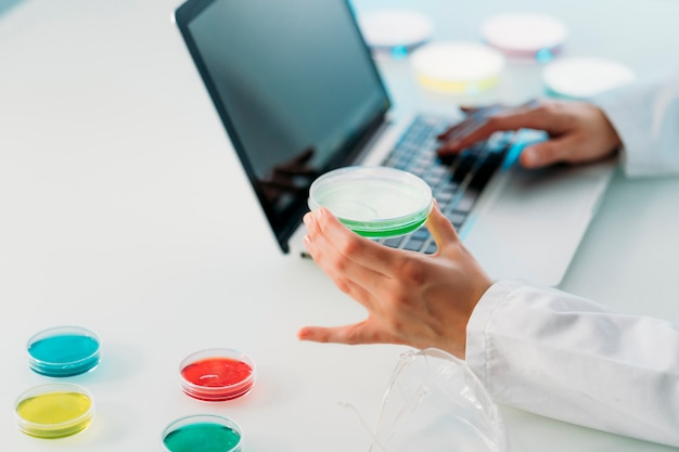 Gros plan d'une femme scientifique travaillant dans un laboratoire avec ordinateur portable et boîte de pétri enquêtant sur le coronavirus