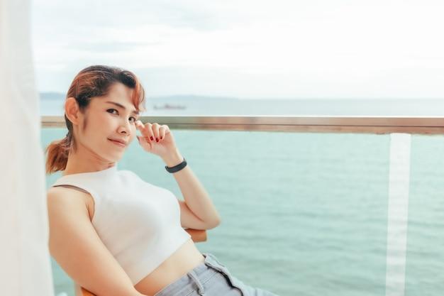Gros plan sur une femme se détendre sur le balcon de l'hôtel avec vue sur la mer en été